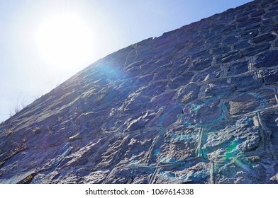 Escalating wall with deep engraved texture on cement pattern background and glare of the sun