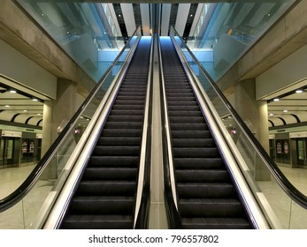 Escalator at an airport with no people. Two escalators in symmetry going up and down inside an airport going from one floor to the other. Modern and sleek interior an airport. Steal, metal, shinny.