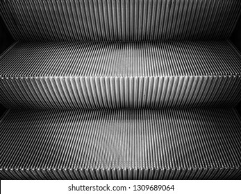 escalator floor two step  with copy space.vertical pattern stairs.striped metallic lines abstract background which has black and white color