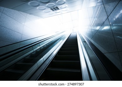 Escalator and light at end of tunnel