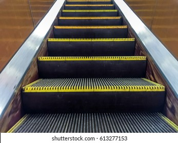 Escalator in metro. Moving up staircase escalator. .Close up to  Moving electric escalator.Close up floor platform electric escalator. yellow bands metal line steel. yellow gray steel line.