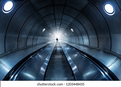 Escalator with a person at the end leads into the light; concept of fear, danger and escape