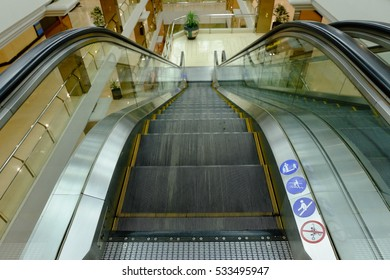 Escalator for scroll down to the floor of a shopping mall. looking a black tone color and white floor.