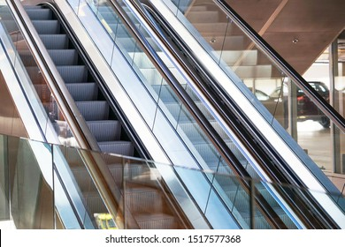 Escalators in an office building. Empty escalator stairs. Modern escalator in shopping mall, Department store escalator. Empty escalator inside a glass building.
