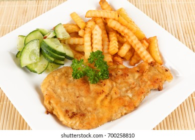 escalope with french fries and cucumbers