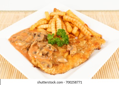 escalope with mushrooms and french fries on a plate