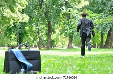Escape from civilization concept - business man running in park away from bag, shoes and tie