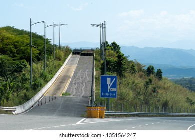 Escape Lane uphill with road sign on dual carriageway highway through mountains in scenic countryside landscape with gravel stones, tires/tyres, reflective cones. Two lane/double lane street/roadway.