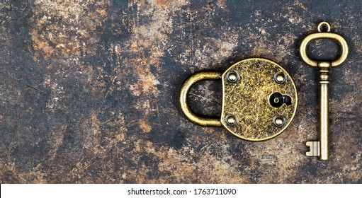 Escape room game concept. Web banner of a vintage gold key and locked padlock on a rusty metal background.
