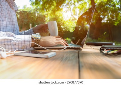 Escaped of office. Business style dressed man sitting at natural country style wooden desk with electronic gadgets around working on laptop drinking coffee sunlight and green terrace on background