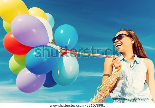 Escaping the reality.  Low angle view of joyful young woman holding colorful balloons and smiling while standing against the blue sky