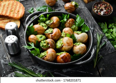 """Escargots de Bourgogne"" - baked snails with garlic, butter and basil. French traditional food. Top view. Free space for your text."