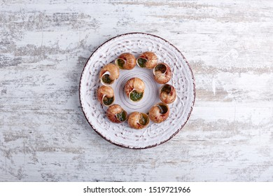 Escargots de Bourgogne - Snails with herbs butter on wooden background.