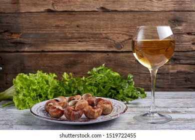Escargots de Bourgogne - Snails with herbs butter on wooden background. Salad. Parsley. Glass of wine.