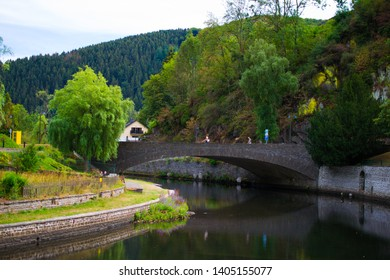 Esch-sur-Sure, Luxembourg; 08/12/2018: Old stone bridge over Sure river with a walkway through the riverside and mountain and trees at the background. Esch Sur Sure, Luxembourg