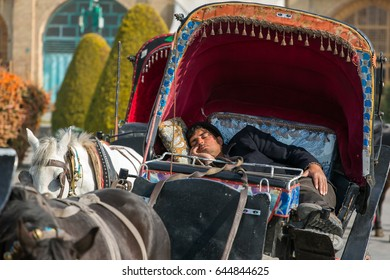 Esfahan, Iran - December 13, 2015: Iranian man sleeps in traditional old fashioned fiacre, horse-driven carriage in Esfahan, Iran.