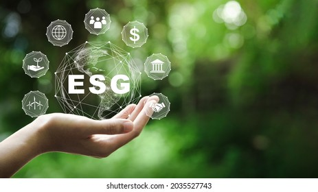 ESG icon concept in the hand for environmental, social, and governance in sustainable and ethical business on the Network connection on a green background.