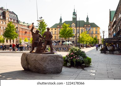 Eskilstuna, Sweden - Aug 24, 2018: Monument over the smiths at fristads square in central Eskilstuna with its city hall in background.