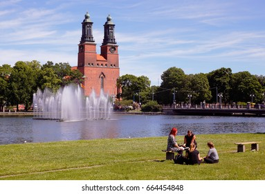 Eskilstuna, Sweden - June 19, 2017: A group of four people sitting in the park at the waterfront in downtown Eskilstuna with the Klosters church in the background.