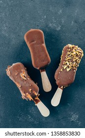 Eskimo ice cream in chocolate glaze on blue background. Yummy sweet food snack treat. Top view, copy space