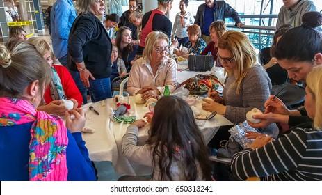 "Eskisehir, Turkey - April 08, 2017: People attending a workshop and exhibition called ""Arzu'nun Bebekleri"" at NeoPlus Outlet Center in Eskisehir. Women creating handmade art dolls in group."