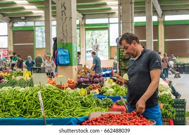 Eskisehir, Turkey - June 15, 2017: People at traditional typical Turkish grocery bazaar in Eskisehir, Turkey. Seller man standing behind his counter.
