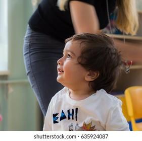 Eskisehir, Turkey - May 05, 2017: Sweet little boy with brown hair and his mother behind in kindergarten classroom