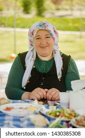 Eskisehir, Turkey - May 24, 2015: Portrait of a happy young woman wearing traditional clothings having picnic on a sunny day with blurry nature background.