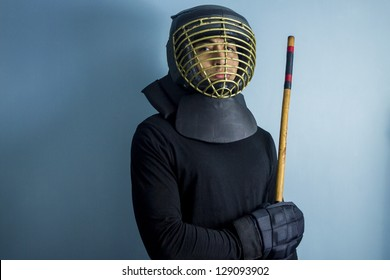 Eskrimador posing in front of a blue wall, wearing protective helmet and gloves and holding a rattan escrima stick