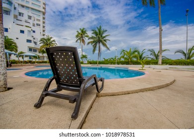 Esmeraldas, Ecuador - March 16, 2016: Beautiful swimming pool with circle form, with a rattan chair in the border in a luxury hotel at Same, Ecuador
