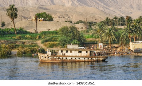 ESNA, EGYPT - JUNE 2, 2019: Old river ship and young Arabs bathing in river Nile, Egypt