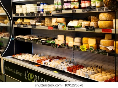 ESPELETTE, FRANCE - AVRIL 19, 2018: Cheese, delicatessen and dairy shop. Assortment of local cheeses- made from goat, sheep or cow milk, seasoned with espelette peppers, famous Ossau-Iraty cheese.