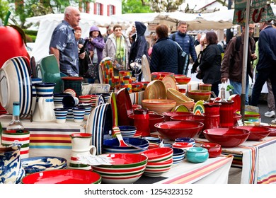 ESPELETTE, FRANCE - AVRIL 25, 2018: Traditional ceramic crockery of French Basque Country for sale at local market. Shoppers  crowd at background.