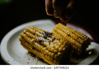 Espiga de milho cozida com manteiga em fundo escuro