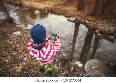 ESPOO, FINLAND - APRIL 20, 2019: Child photographing a forest stream