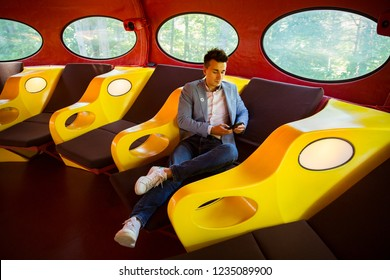 ESPOO, FINLAND - SEP 02, 2018: The utopian plastic house Futuro, designed by Finnish architect Matti Suuronen in Espoo Museum of Modern Art, interior. Man sitting on lounger
