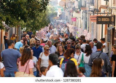 Esporles Mallorca, Spain / October 14, 2018: Visitors walk near the bakery stands during the Fira Dolca local gastronomy fair in the village of Esporles in the Spanish island of Mallorca