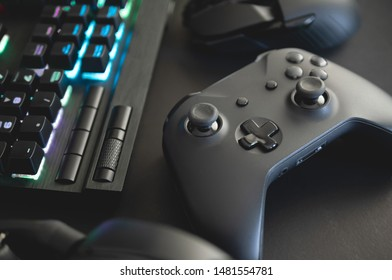 e-sport concept with gaming gear, mouse, keyboard, joystick, headset, mobile joystick, in ear headphone and mouse pad on black table background.