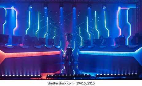 eSports Winner Trophy Standing on a Stage in the Middle of the Computer Video Games Championship Arena. Two Rows of PC for Competing Teams. Stylish Neon Lights with Cool Design.