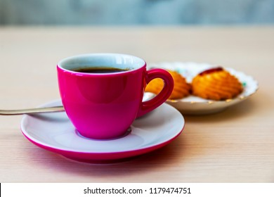 Espresso coffee in a bright pink porcelain cup and cookies on a saucer