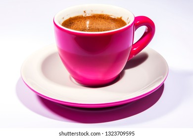 Espresso coffee in a bright pink porcelain cup on the table