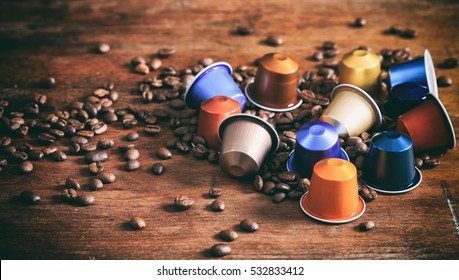 Espresso coffee capsules, pods and coffee beans on wooden background
