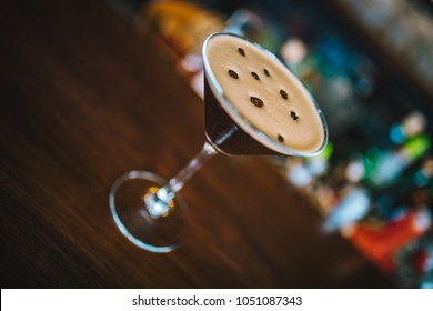 Espresso coffee martini cocktail with coffee beans on the bar desk with blur background