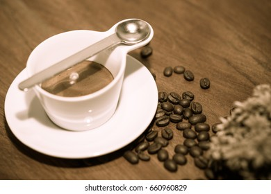 Espresso coffee and roasted coffee beans on wooden table background.