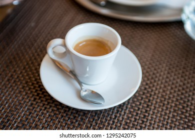 espresso coffee in a white cup on a table in a cafe