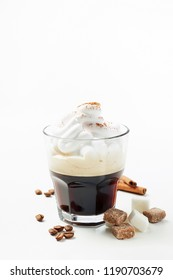 Espresso con panna or Vienna coffee. Two shots of espresso with whipped cream, cinnamon, coffee beans and sugar cubes. Close up view on white background with copy space