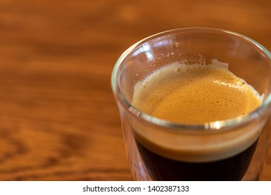 espresso cream close up on glas on wooden table