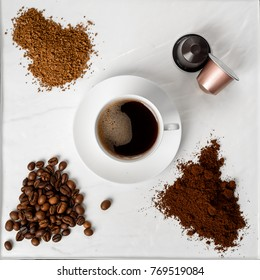 Espresso cup, coffee beans, ground coffee, coffee capsule and instant coffee on a white background