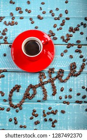 Espresso cup of coffee with the word coffee spelt with coffee beans on a wooden background