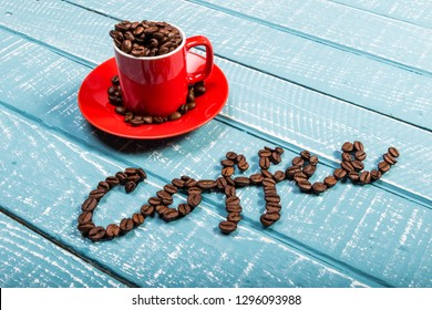 An espresso cup full of coffee beans on a weathered table with the word coffee spelt out
